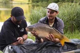 Deux pêcheurs ayant pêcher une belle carpe