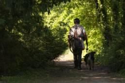 Pêcheur dans un sentier avec son chien, sa canne à pêche et son épuisette dans le dos