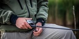 canne à pêche à moulinet dans les mains d'un pêcheur
