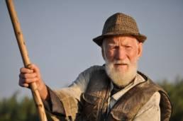 Viel homme qui pêche avec une canne de fortune